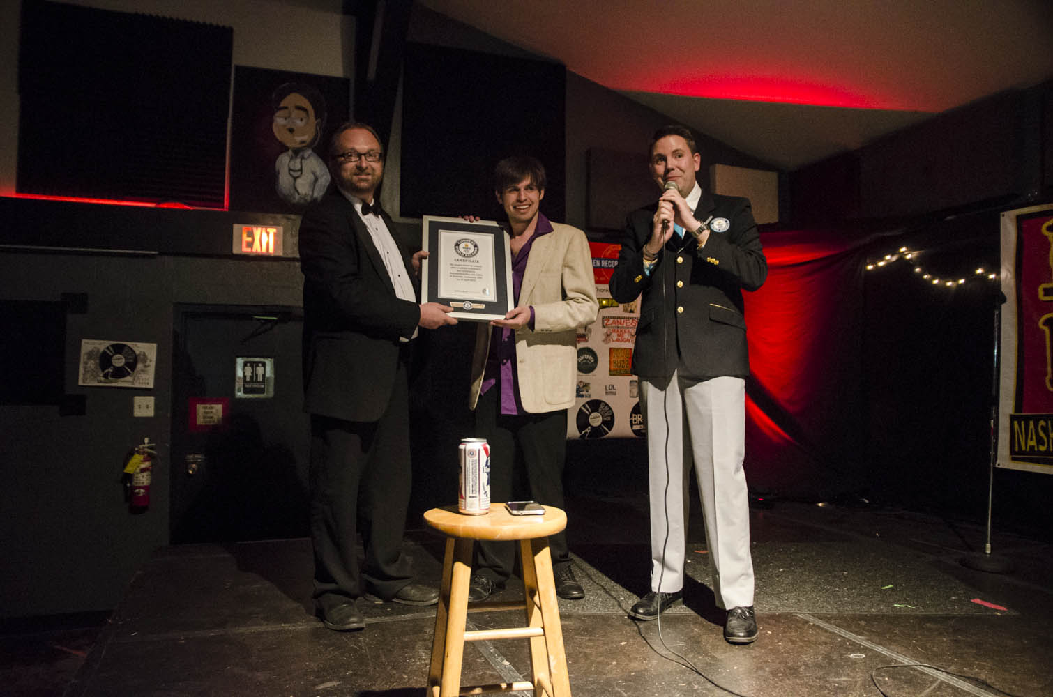 Official GUINNESS WORLD RECORDS™ adjudicator Michael Empric presents the framed certificate to Chad Riden (left) and DJ Buckley (center).